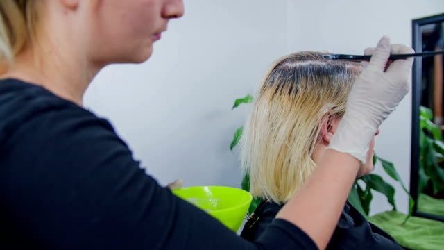 Costumer comes to get hair done Slow motion RAW close up footage of a hear dresser putting the colour in the woman hair in the professional salon. highlights hair stock videos & royalty-free footage