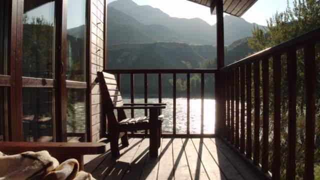 gemütlicher balkon eines landhauses mit bergblick auf die landschaft am sonnigen tag - landhaus stock-videos und b-roll-filmmaterial