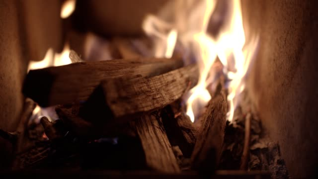 POV. Cosy home relaxation in front of the fireplace. Celebration time. Fireplace with burning woods close-up.