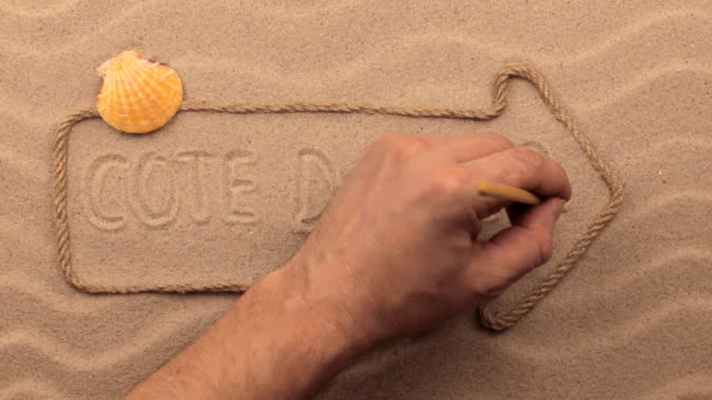 Cote d'azur inscription written by hand on the sand, in the pointer made from rope. video