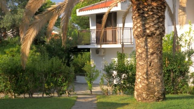 庭、夏のシーンの椰子の木とコテージ - ヴィラ点の映像素材/bロール