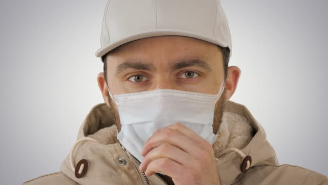 Coughing casual man in medical mask on gradient background Close up. Coughing casual man in medical mask on gradient background. Professional shot in 4K resolution. 53. You can use it e.g. in your medical, commercial video, business, presentation, broadcast emphysema stock videos & royalty-free footage