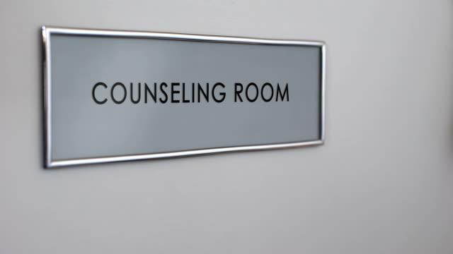 vídeos y material grabado en eventos de stock de puerta de la habitación de consejería, mano golpeando closeup, terapia familiar, grupo de apoyo - profesional de salud mental