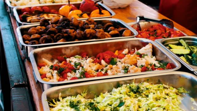 vídeos de stock e filmes b-roll de counter distributes food in plastic plates in which mushrooms, salad and porridge. street food. food festival - cantina