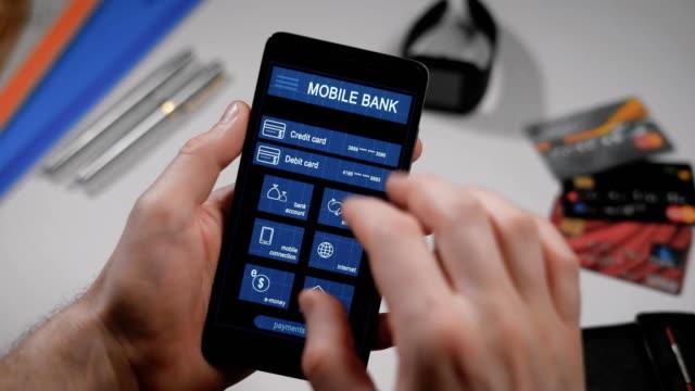 vídeos de stock, filmes e b-roll de contador pagamento via aplicativo banco móvel no smartphone. um homem transfere o dinheiro do seu cartão de crédito para outra pessoa - log on