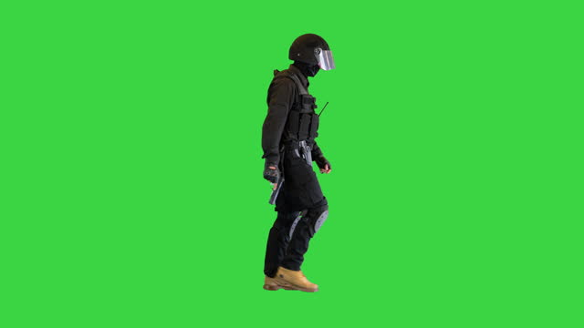 Counter terrorist squad fighter walking with a pistol in a hand on a Green Screen, Chroma Key