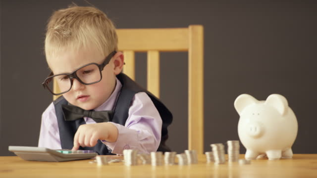 Counting all the Money Cute toddler dressed up in business clothing counts money using a calculator in front of a blackboard background. piggy bank stock videos & royalty-free footage