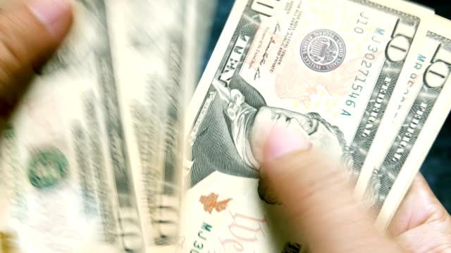 räknar pengar i hand – nya $10 us-dollar räkningar. närbild av en affärsman händer räknar liten amerikansk räkningar sedel. - spendera pengar bildbanksvideor och videomaterial från bakom kulisserna