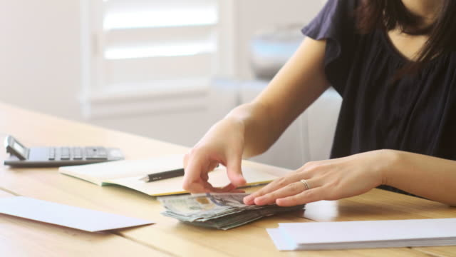 Counting Money A woman organizing and counting money on a table. loan stock videos & royalty-free footage