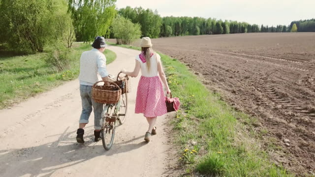 country couple hugging on the field. - cestino della bicicletta video stock e b–roll