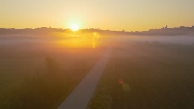 AERIAL Country road at sunrise Aerial shot of a morning mist covering country road along cultivated fields at sunrise. Also available in 4K resolution. horizon over land stock videos & royalty-free footage