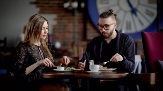 A couple, a man and a woman in a modern restaurant, have lunch or dinner. A man and a woman enjoy food and have a social conversation. In love, they laugh because they have a date video
