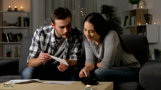 Couple accounting checking receipts at home