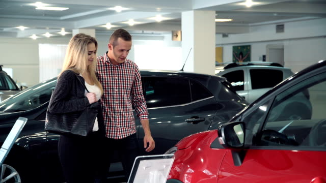 Couple admiring a red car in a showroom Couple admiring a red car in a showroom as they shop for a new vehicle smiling with appreciation as they make a selection. FullHD car shopping stock videos & royalty-free footage