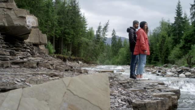 vídeos de stock e filmes b-roll de couple admiring the view. mountain landscape with river - man admires forest