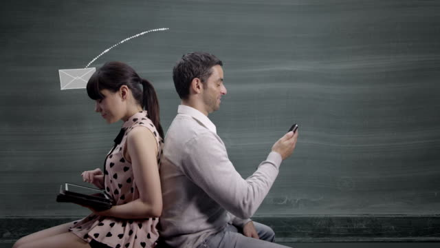 Couple against blackboard send text messages and emails