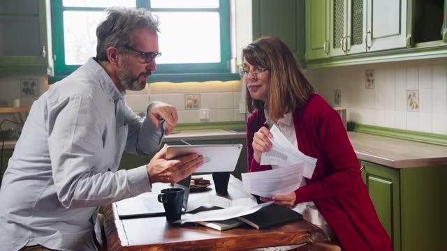 coppia che analizza le finanze a casa insieme - coppia eterosessuale video stock e b–roll