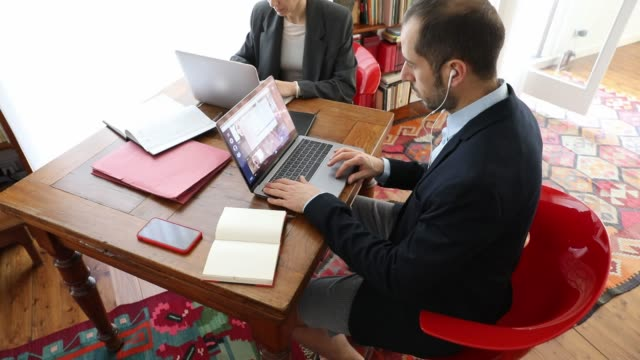 Couple and business partner workin at home together in video conference during Covid-19 lockdown Couple and business partner workin at home together in video conference during Covid-19 lockdown emergency. businesswear stock videos & royalty-free footage