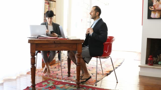 couple and business partner workin at home together in video conference during covid-19 lockdown - pantaloncini video stock e b–roll