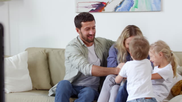 Couple and Children Play Fighting over Remote Control