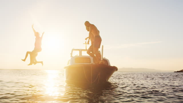 SLO MO Couple and their friends jumping off a boat at sunset video