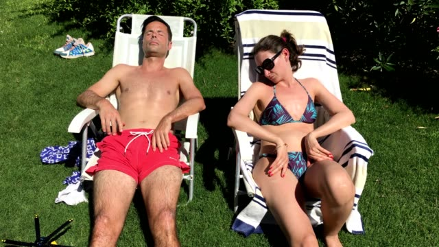 couple asleep sunbathing outside - vitamin d стоковые видео и кадры b-roll
