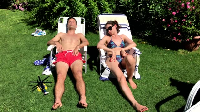 Couple asleep while sunbathing during summer vacations video