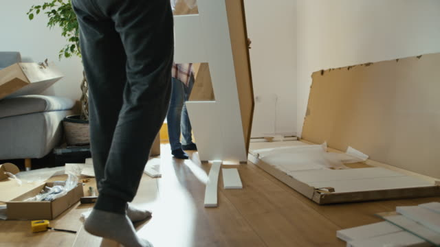 slo mo couple assembling a new furniture at home - meble filmów i materiałów b-roll