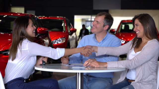 Couple at a dealership closing a deal to with a saleswoman video