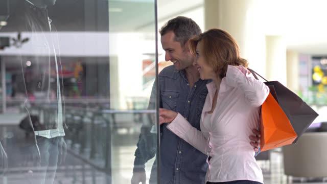 par på en mall ser en fönster butik och pekar outfit - spendera pengar bildbanksvideor och videomaterial från bakom kulisserna