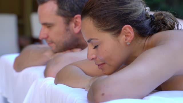 Pareja en un spa recibiendo un masaje de espalda y mirando relajada - vídeo