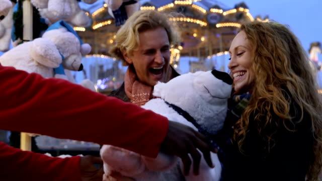 zu zweit am weihnachtsmarkt spielzeuge zu gewinnen - weihnachtsmarkt stock-videos und b-roll-filmmaterial