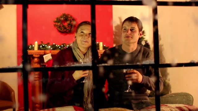 paar am fenster, trinkt glühwein weihnachten - weihnachtsstrumpf stock-videos und b-roll-filmmaterial