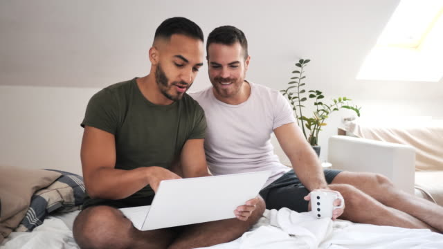 LGBT couple at home using internet and laptop to chat with friends Gay couple at home - 60 fps video, suitable for high quality slow motion shopping online stock videos & royalty-free footage