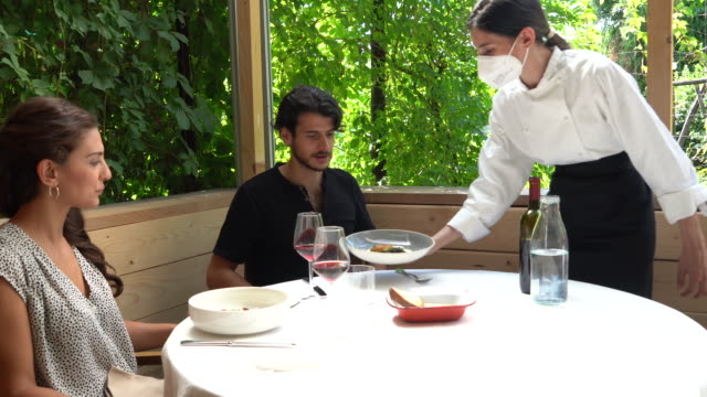 Couple at restaurant table, chef serving main dishes