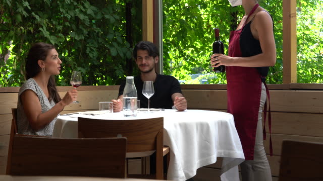 Couple at restaurant table, waitress serving red wine