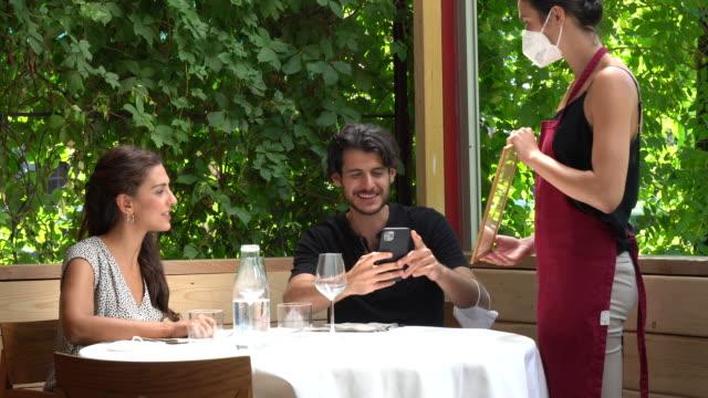 paar am restauranttisch, kellnerin zeigt das menü - bedienungspersonal stock-videos und b-roll-filmmaterial