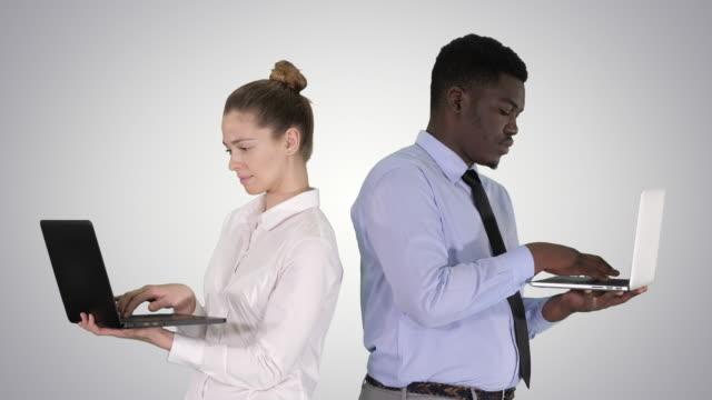 paar zurück zu hinten stehend und arbeiten auf laptops auf gradienten hintergrund - rücken an rücken stock-videos und b-roll-filmmaterial