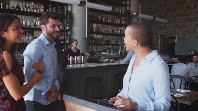 paar wird von maitre d mit digitalen tablet begrüßt, wie sie im restaurant ankommen - eine reservierung vornehmen stock-videos und b-roll-filmmaterial