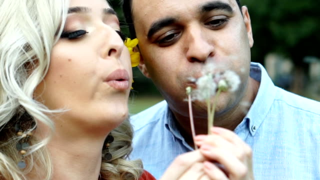 Couple blowing dandelion
