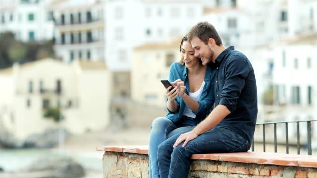 vídeos y material grabado en eventos de stock de pareja de navegación en el teléfono sobre una repisa - viajes familiares