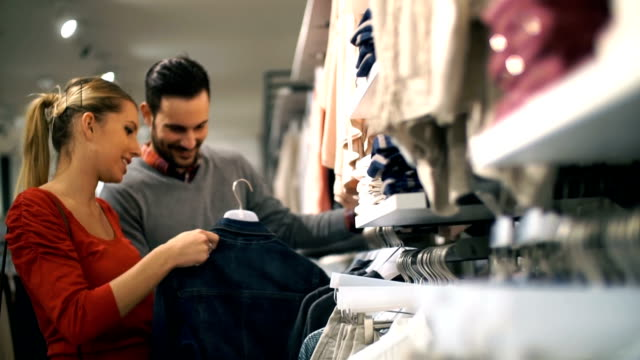 Pareja de compras en una tienda de ropa de venta al por menor. - vídeo