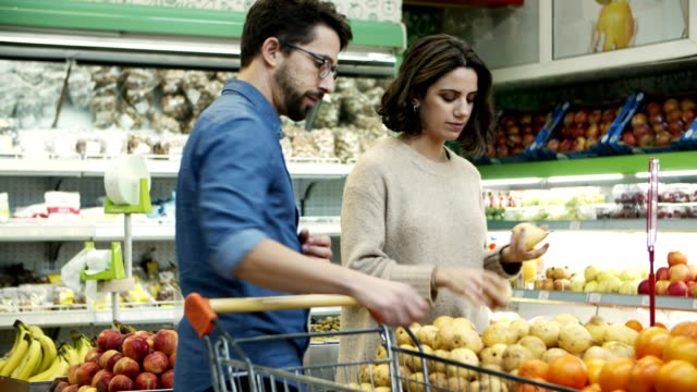 Couple buying fresh fruits in supermarket