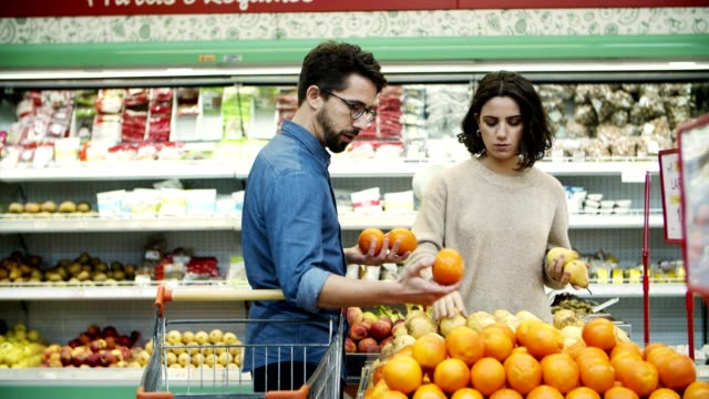 Couple buying fruits in supermarket