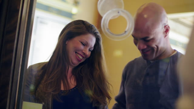Couple buying movie tickets seen from box office video