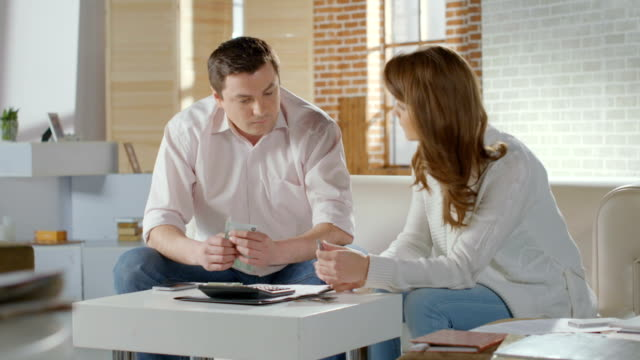 Couple calculating income and expenses, low family budget, money