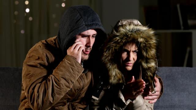 coppia che chiama l'assicurazione sui danni al riscaldatore - abiti pesanti video stock e b–roll