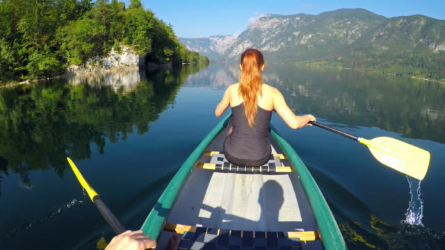 Couple canoeing on a lake towards the mountains video