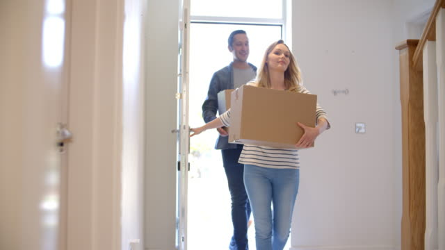 couple carrying boxes into new home on moving day - new home stock videos & royalty-free footage