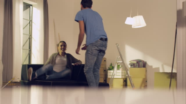 couple carrying couch into new apartment and sit down - möbel bildbanksvideor och videomaterial från bakom kulisserna